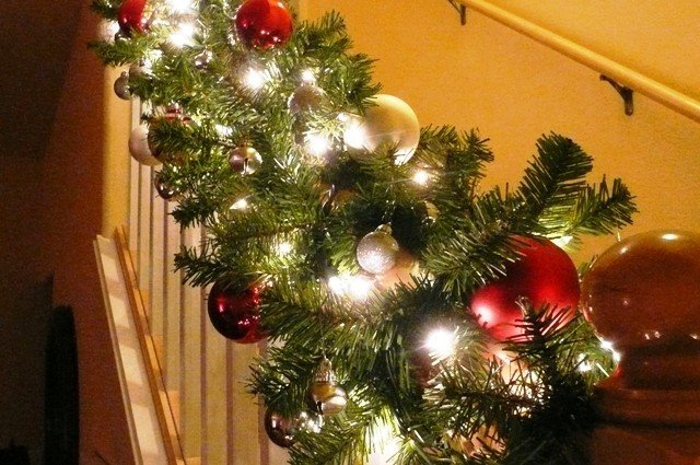 Banister Decorated for Christmas With Lit Garland and Ornaments