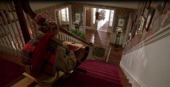Kevin riding down the front staircase in the movie, Home Alone