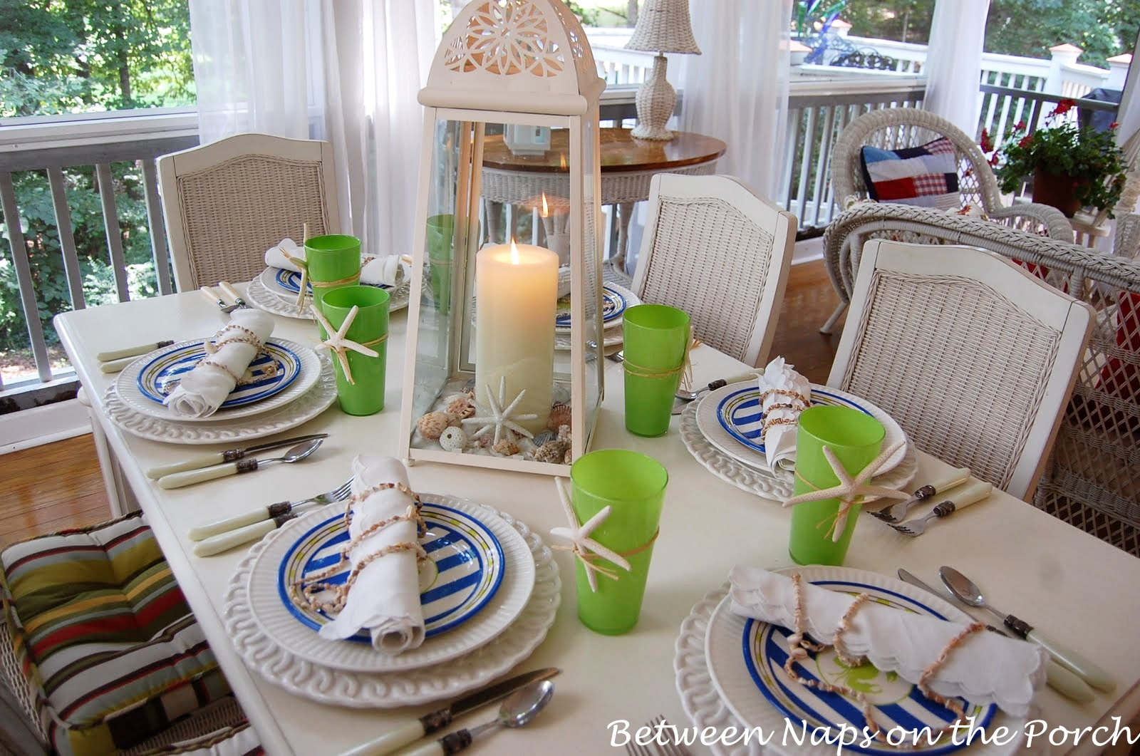 beach themed tablescape setting with a lighthouse style lantern centerpiece and shell napkin holders. Black Bedroom Furniture Sets. Home Design Ideas