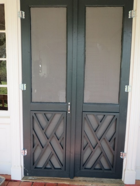 Screen doors on back porch with Chippendale Design