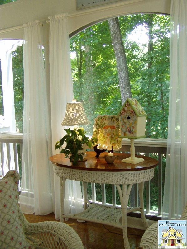 Screened Porch with Wicker Furniture and Mosaic Birdhouse