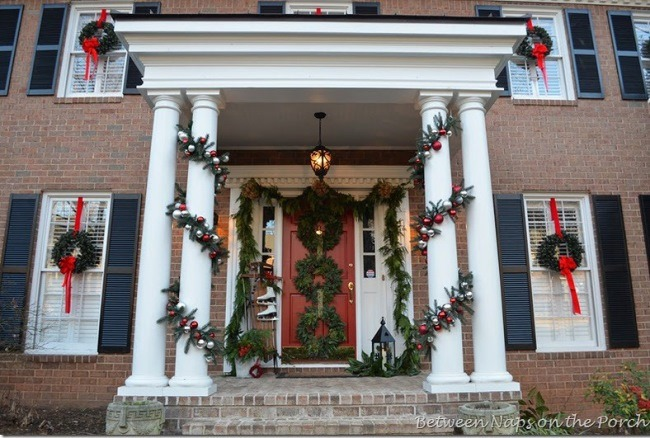 Porch decorated with garland and wreaths for Christmas
