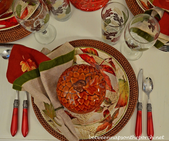 Fall Table Setting with Leaf Themed Dishware and Red Flatware