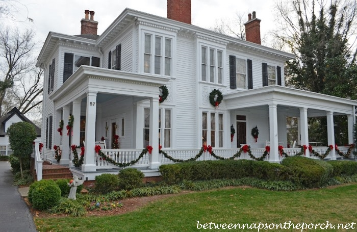 porch decorated with garland draped on porch_wm - Christmas Porch Railing Decorations
