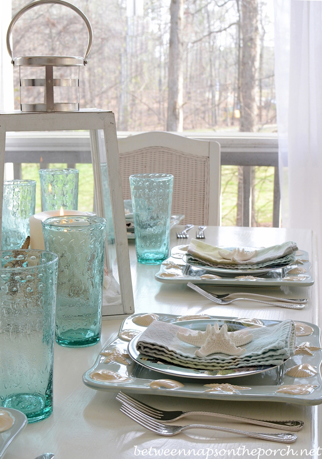 Nautical Beach Table Setting With Shell And Sailboat Plates