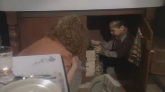 A Christmas Story Scene with Randy Hiding Under Kitchen Cabinet
