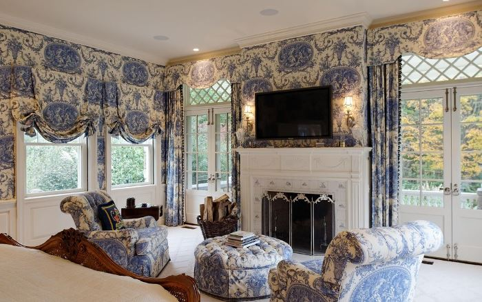 Blue and White Bedroom with Seating Area and Fireplace
