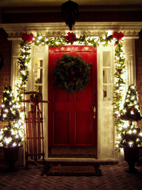 Porch Decorated for Christmas with Lit Garland and Sled