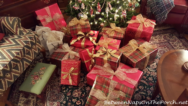 Christmas presents wrapped in green and red plaid paper with gold ribbon