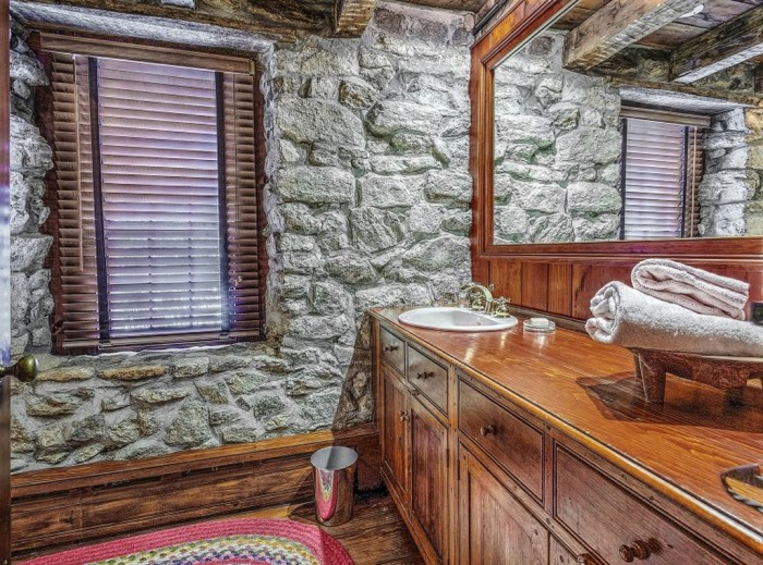 Bath with Stone Walls and Wood Cabinetry
