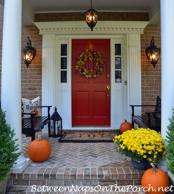 halloween-porch-with-pumpkins-black-benches-pillow-and-lantern