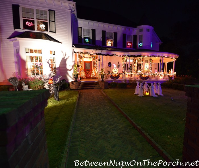 victorian-home-lit-for-halloween-ghosts-and-witches-on-the-lawn_wm