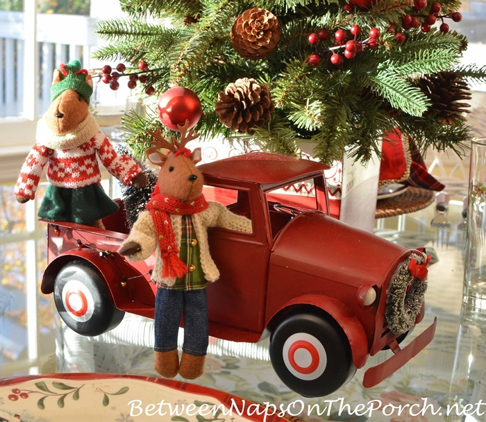 red christmas truck and station wagon with lit tree and wreath for