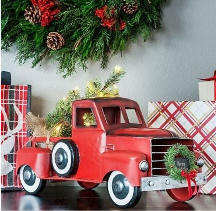 vintage red truck with wreath and lit tree