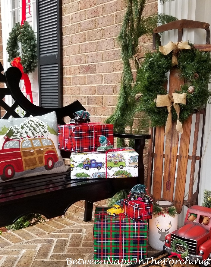 Christmas Porch with Sled and Presents with Cars Bringing Home the Tree