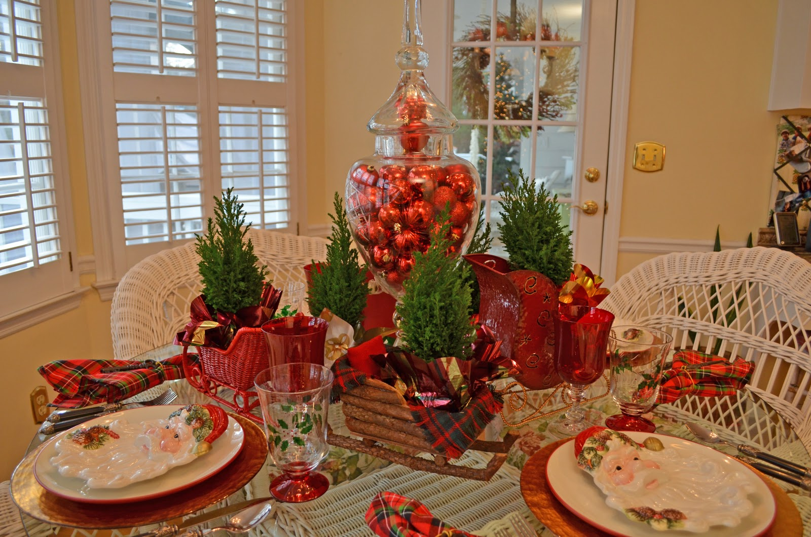 Santa themed tablescape with santa plates and a sleigh Small christmas centerpieces